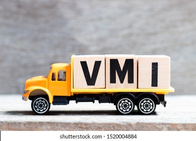 Truck hold letter block in word VMI (abbreviation of vendor managed inventory) on wood background
