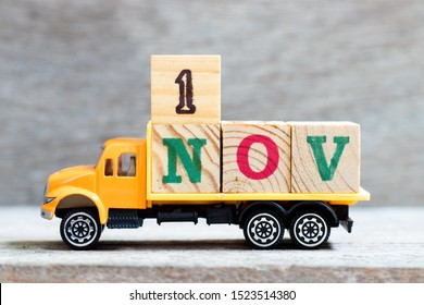 Truck hold letter block in word 1nov on wood background (Concept for date 1 month November)