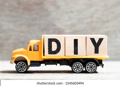 Truck hold letter block in word DIY (abbreviation of do it yourself) on wood background