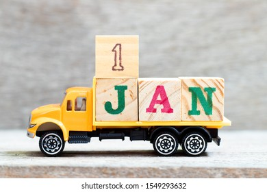 Truck hold letter block in word 1jan on wood background (Concept for date 1 month January) First day of the new year