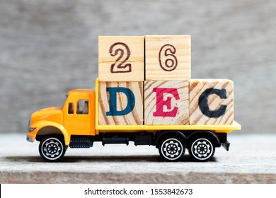 Truck hold letter block in word 26dec on wood background (Concept for date 26 month December)
