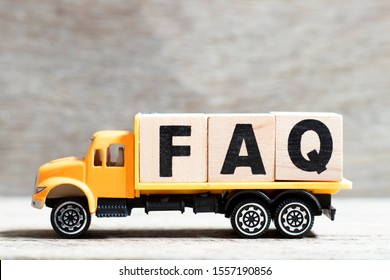 Truck hold letter block in word FAQ (Abbreviation of Frequently Asked Questions) on wood background