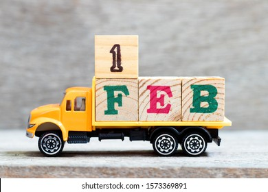 Truck hold letter block in word 1feb on wood background (Concept for date 1 month February)