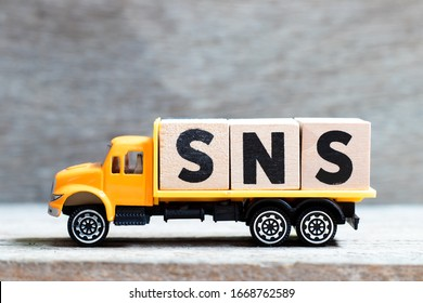 Truck hold letter block in word SNS (abbreviation of Social Networking Site or sorry not sorry) on wood background