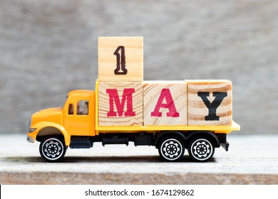 Truck hold letter block in word 1may on wood background (Concept for date 1 month may)