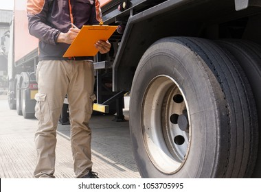 Truck inspection and safety. Truck driver holding clipboard is checking wheels truck.