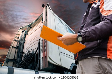 Truck inspection and safety. Truck driver holding clipboard is checking safety a truck.