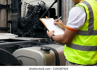 Truck inspection and safety. Truck driver writing  on clipboard with checking truck fuel tank.