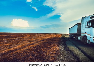 truck KAMAZ is driving along the highway on the background the sky