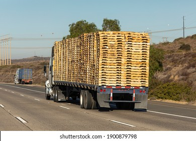 Truck loaded high with stacks of pallets traveling on a freeway