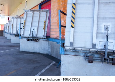 Truck loading docks at commercial building. Overhead door, dock leveler, and dock seals - Shutterstock ID 1886633332