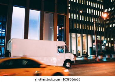 Truck of logistic shipping company on city road delivering goods for order quickly in time at night, truck move speedily on avenue transporting and distributing stuff for postal service in metropolis