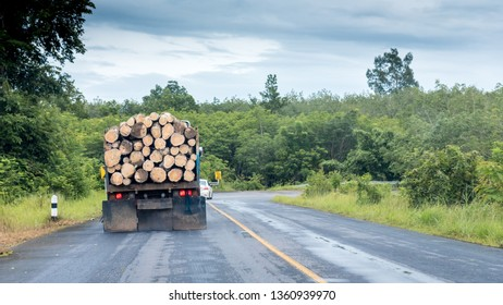 Truck with logs on smail highway in Thailand