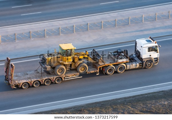 Truck with a long trailer platform for transporting heavy machinery, loaded tractor with a bucket. Highway transportation