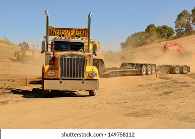 Truck and low boy trailer leaving a construction site after delivering its oversized load