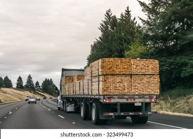 a truck  of lumbers moving on the road.