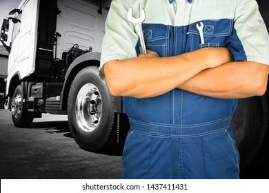 Truck maintenance and repairing. Professional auto mechanic holding wrench for repairing semi truck.