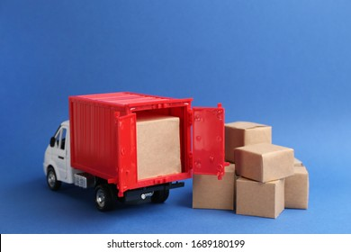 Truck model and carton boxes on blue background. Courier service