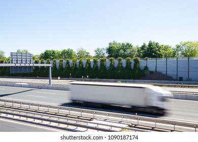 Truck with motion blur on a highway in front of a modern noise protection wall