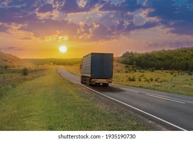 Truck moves along a suburban highway at sunset in summer.
