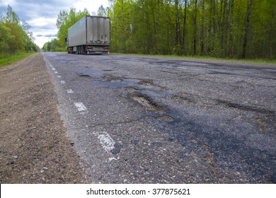 Truck moving on a broken road with potholes