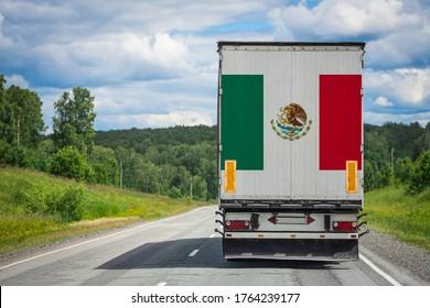 Ein Lastwagen mit der Flagge Mexikos An der Hintertür abgebildet, transportiert man Waren in ein anderes Land entlang der Autobahn. Konzept der Ausfuhr-Einfuhr, Beförderung, Inlandslieferung von Waren
