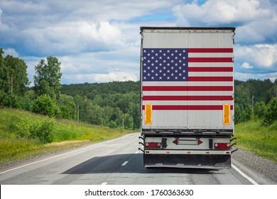 Ein Lastwagen mit der Nationalflagge der USA, der auf der Hintertür abgebildet ist, transportiert Waren in ein anderes Land entlang der Autobahn. Konzept der Ausfuhr-Einfuhr, Beförderung, Inlandslieferung von Waren