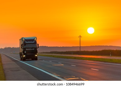 truck on the highway in the rays of the rising sun at dawn