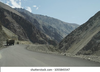 Truck on narrow, twisting road along the Indus River in deep valley, Ladakh, India