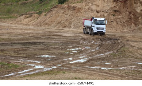 Truck on sand and gravel outcrop site.