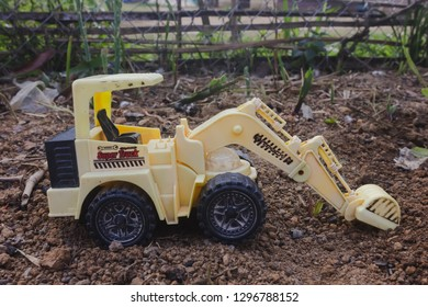 truck ot tracktor digger on land outside in ground lifstle of children playing toy with car on background