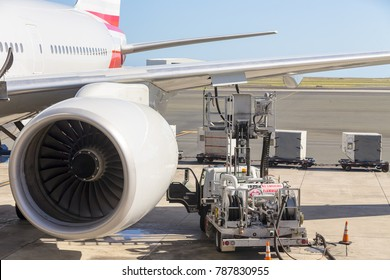 Truck parked under an aircraft wing refuelling the tanks with aviation fuel through an open flap with a turbo engine in the foreground during servicing at the airport