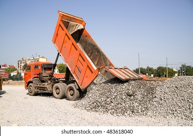 The truck pours the crushed body on the road construction