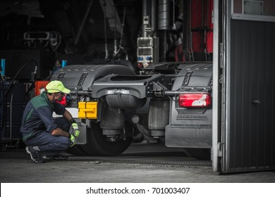 Truck Service Technician Job. Caucasian Truck Mechanic Checking on Semi Truck Tractor.