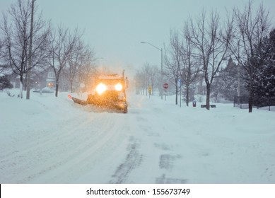 Truck with a snow plow clearing a suburban street