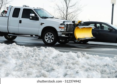 truck with snowplow installed in parking lot with snow removed