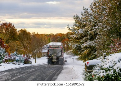 Truck with snowplow plowing suburban Midwestern street after first snowfall; view from the back; some trees preserve their colorful fall leaves; Missouri