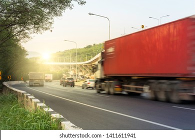 Truck with space for text driving fast on the countryside road with mountain against sunrise