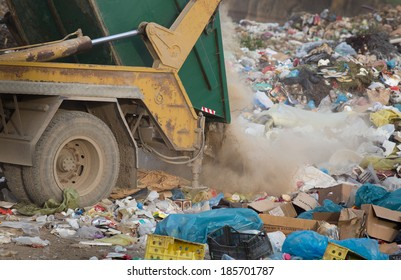 Truck tipping garbage from container on junk yard