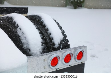 Truck tires and brake lights in a heavy snow storm.