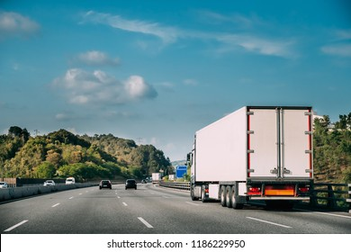 Truck Or Traction Unit In Motion On Road, Freeway. Asphalt Motorway Highway Against Background Of Forest Landscape. Business Transportation And Trucking Industry.