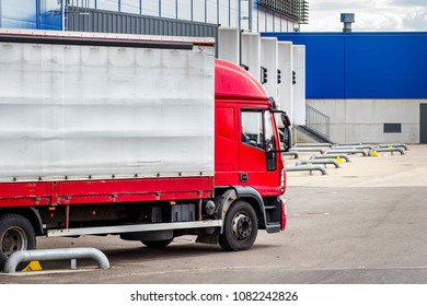 Truck with trailer on loading in logistics center. Transportation of goods. Unloading of goods near large shopping center. Cargo container near the ramp of logistics
