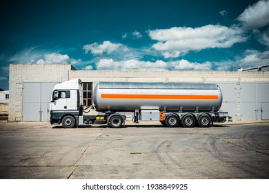 Truck with trailer, tank with flammable liquid, sunny day outside, metallic color container, blue sky with white clouds, gravel