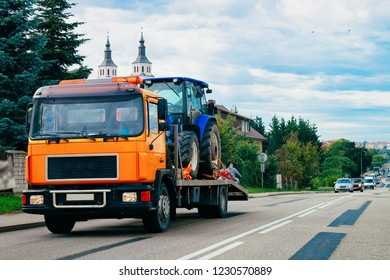 Truck trailer transporter with hauler carrying agricultural tractor on the road in Poland.