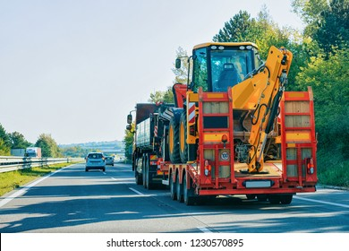 Truck trailer transporter with hauler carrying agricultural tractor on the road, in Slovenia.