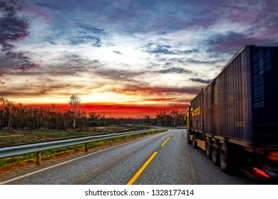 Truck transport on the road at sunset.
