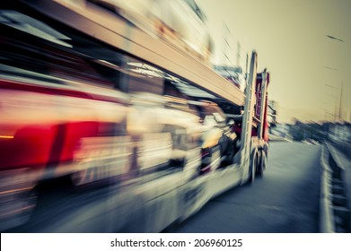 Truck transports cars, track in motion.