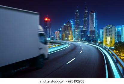 Truck traveling on road at night - speed and delivery concept.