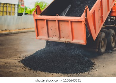 truck unloads fresh asphalt into the spreader on big road in the city
