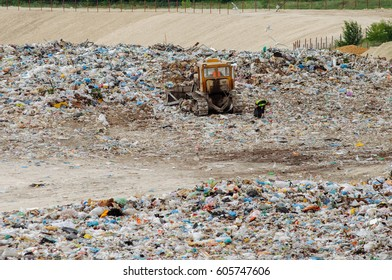 Truck working in landfill with birds looking for food. Garbage on the city dump. Soil pollution. Environmental protection. Waste.